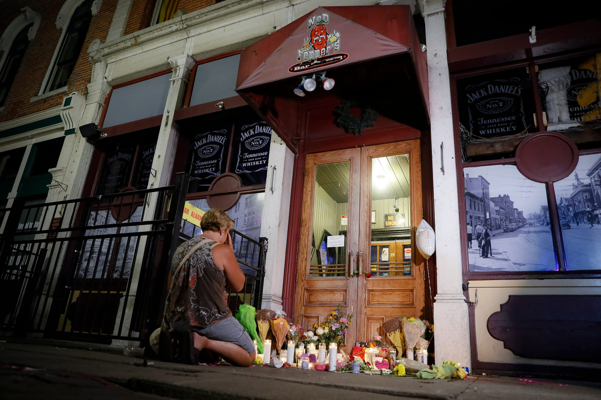 Mourners visit a makeshift memorial outside Ned Peppers bar following a vigil at the scene of a mass shooting, Sunday, Aug. 4, 2019, in Dayton, Ohio.