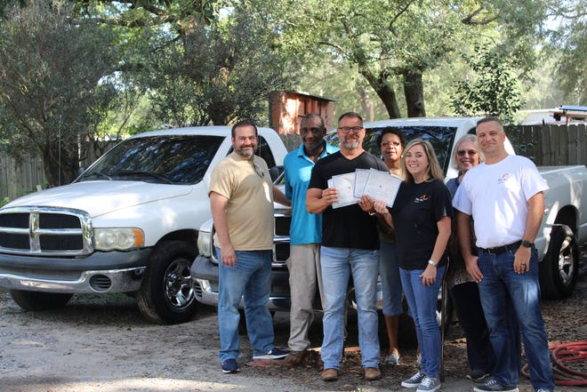 Gulfside Landscaping donates four pick-up trucks to The Arc Gateway.