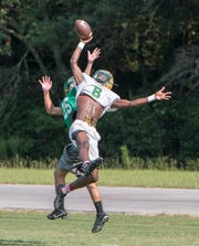 Damarius McGhee (6) leaps to break up a pass during football practice at Pensacola Catholic High School in Pensacola on Wednesday, July 31, 2019.