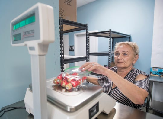 Tatyana Lobanova weighs and bags candies at the new Merefa Eastern-Europe Grocery Store on N. Davis Highway in Pensacola on Monday, August 5, 2019.  The store is named after owner Zoya Iosilevich's Ukrainian hometown of Merefa.