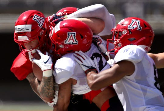 Receiver Jaden Mitchell, a true freshman, gets forced out of bounds by a trio of Wildcat defenders after his catch and run during Saturday's scrimmage at Arizona Stadium.