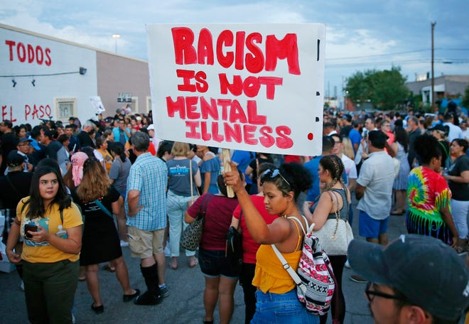 A woman holds a sign after a silent march to Las Americas Immigrant Advocacy Center for the victims of the Walmart shootings in El Paso August 4, 2019. Twenty people were killed and more than two dozen were injured in a mass shooting at Walmart on Saturday.