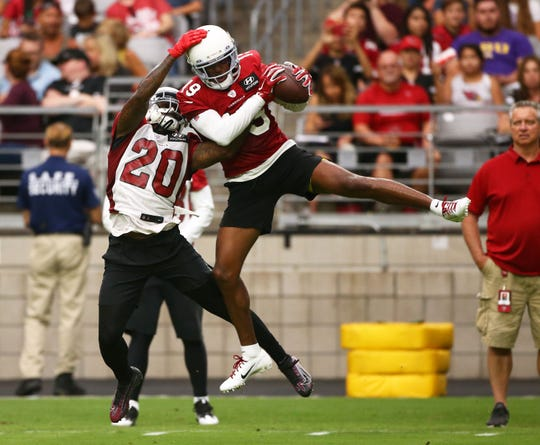 Arizona Cardinals wide receiver KeeSean Johnson (19) makes a catch against cornerback Tramaine Brock (20) during training camp on July 26, 2019 in Glendale, Ariz.
