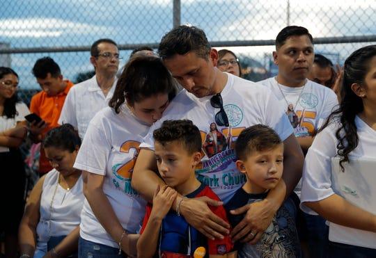 Gabriela López y su esposo Roberto, abrazan a sus hijos durante la vigilia celebrada el 4 de agosto, 2019, en memoria del as víctimas del tiroteo en El Paso, Texas.