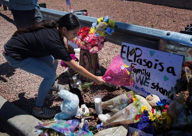 Una mujer coloca flores en una altar improvisado, en memoria de las víctimas de tiroteo en El Paso, Texas.