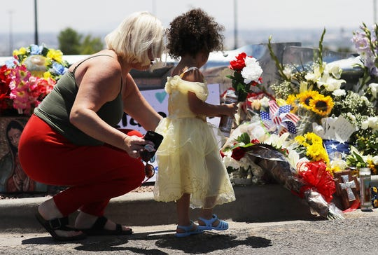 Persons in El Paso, Texas mourn and offer flowers in memory of the victims of the mass shooting Aug. 3 at a Walmart in the city.
