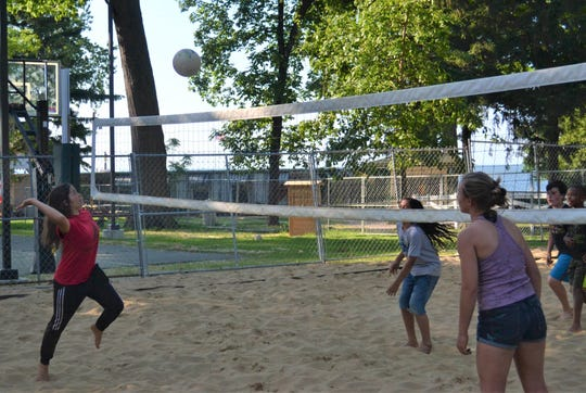 A group of kids play on the newly renovated sand volleyball court at Lakeside.