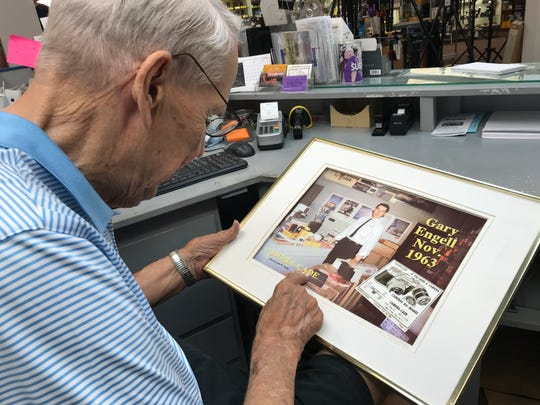 Gary Engell looks at a framed photo of him in 1963.