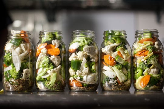 Mixed vegetables sit in jars before brine is poured over them as part of the canning process.