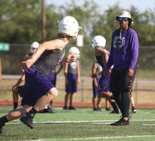 An Irion County High School football player goes out for a pass while coach Brandon Flowers gives encouragement during the first day of workouts Aug. 5, 2019 at Wolfenbarger Field in Mertzon.
