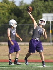 An Irion County High School football player prepares to release a pass during a drill at the first day of workouts Aug. 5, 2019 at Wolfenbarger Field in Mertzon.