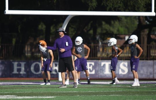 Irion County High School assistant football coach John Morrow conducts warmup drills during the first day of workouts Aug. 5, 2019 at Wolfenbarger Field in Mertzon.