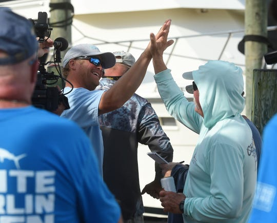 Nate Walker (left) celebrates after catching the first eligible white marlin of the 2019 White Marlin Open on Monday, Aug. 5, 2019.