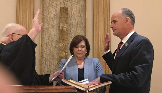 Judge Harmon Drew Jr., of the 2nd Circuit Court of Appeal, swears in Bossier Sheriff Julian Whittington as 74th president of the Louisiana Sheriff's Association as Whittington's wife, Melissa Whittington, holds the family Bible for the ceremony in Baton Rouge.