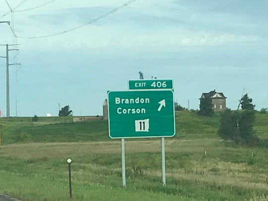 A highway sign with South Dakota shown upside down.