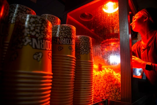 Ryenn Stegenga fills up a popcorn bucket at the Verne Drive-In, Friday, Aug. 2.