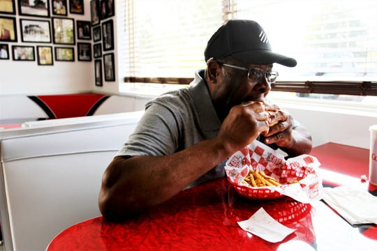 Garland Adams takes a bite of a burger at Red's Giant Hamburg Monday, Aug. 5, 2019.