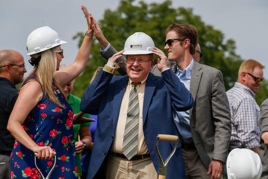 Springfield Mayor Ken McClure, center, adjusts his hard hat as Alina Lehnert, left, high-fives Marshall Kinne during a groundbreaking ceremony for a new early childhood center. Lehnert and Kinne were co-chairs of the campaign committee for the $168 million bond issue approved by voters in April.