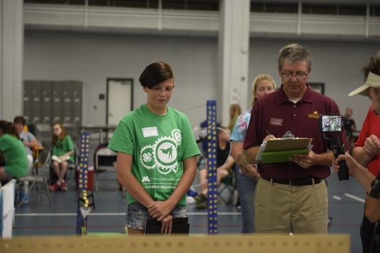 Mackenzie Stepka, 13, of Rice stands next to a judge at the Minnesota 4-H Design Engineering Challenge while she discusses her team's machine. The challenge was Monday, Aug. 5, 2019, at St. Cloud State University's Halenbeck Hall.