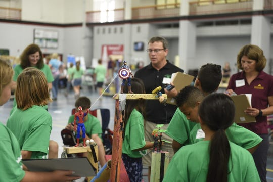 4-H students from Washington County talk Monday, Aug. 5, 2019, with judges about their superhero-themed machine at the Minnesota 4-H Engineering Design Challenge at St. Cloud State University.