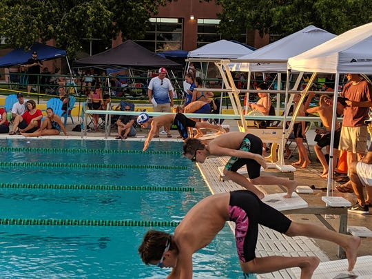 Youth swimmers take off from the blocks during a swim competition in Mesquite last week.