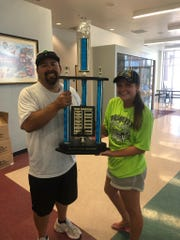 """Nick Montoya, left, the director of Athletics and Leisure Services for the City of Mesquite, holds a trophy with Markell Ludvigson, head coach of the city's """"Manta Rays"""" swim team."""