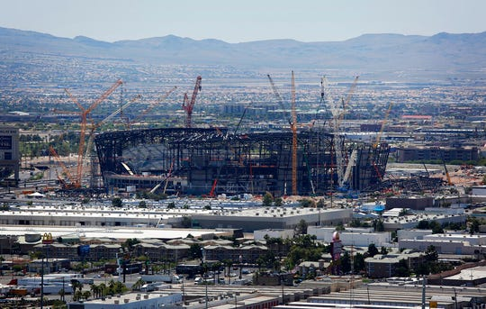 FILE - In this June 4, 2019, file photo, construction cranes surround the football stadium under construction in Las Vegas. The $1.9 billion stadium being built in Las Vegas for the relocated NFL Raiders team is being named for Allegiant Travel Co. Officials made the announcement Monday, Aug. 5, 2019, during a ceremony marking installation of the final steel beam for the roof of the 65,000-seat indoor stadium just off the Las Vegas Strip. (AP Photo/John Locher, File)