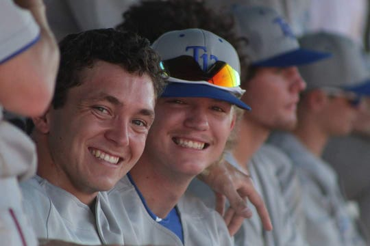 Post 13 players Joe Ruth and Caleb Carter in the dugout during a game.