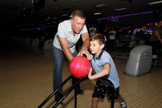 Sean Mitchell, left, helps his son Ethan at the Glow Bowling Birthday Party at SuperPlay USA for the St. Lucie County Early Learning Coalition.