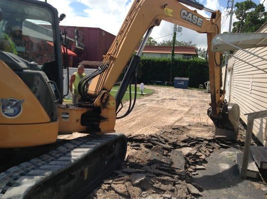 Bill Von Itter watches as Jason Cservak, with Sunshine Land Design of Stuart, usesan excavator to digup the old driveway at The Barn Theatre in Stuart.