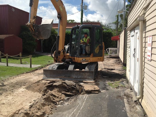 Jason Cservak, a supervisor with Sunshine Land Design of Stuart, usesan excavator to digup the old driveway at The Barn Theatre in Stuart.
