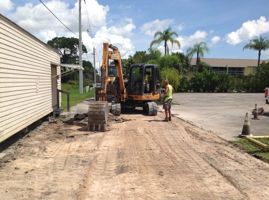 Jason Cservak, with Sunshine Land Design of Stuart, usesan excavator to digup the old driveway at The Barn Theatre in Stuart, as his coworker  Bill Von Itter looks on.