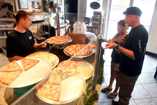 """John Chirco (left) talks Linda Moore and Richard Noory, owners of the Kilted Mermaid in Vero Beach, through all the different types of pizza available at Pizza Mia on Monday, Aug. 5, 2019. A Pizza Mia employee was diagnosed with the Hepatitis A virus prompting Indian River County Department of Health officials to urge anyone who ate there between July 19 and July 23 to get vaccinated and be watching for any symptoms of the virus. """"We love this place, we come here often and so we are going to show our continued support,"""" said Linda Moore. Pizza Mia has been cleared to continue selling food and drinks after officials determined there was no link to the virus found in any food products."""