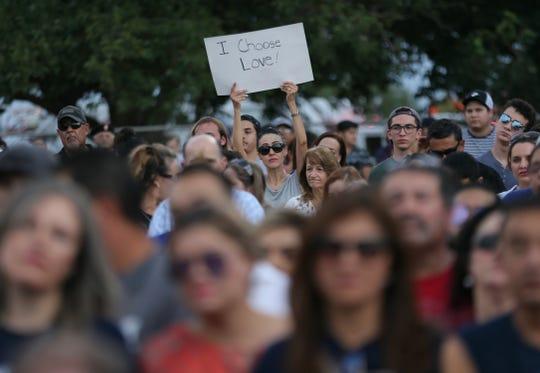 A mourner holds up a sign Sunday at Hope Border Institute Interfaith vigil at Ponder Park.