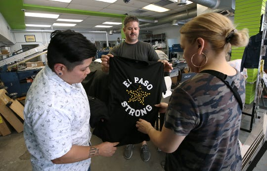 Lisa Basa, left, and Ana Rodriguez buy El Paso Strong t-shirts from Proper Printshop's Alan Hodson just after they were printed Tuesday, August, 5, 2019 at his shop in central El Paso. The proceeds from the sales of the shirts will be donated to the El Paso Community Foundation's El Paso Shooting Victim's Fund.