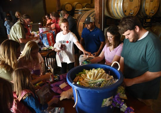 Stephanie Arnold, co-founder of The Homeless Period Project in Greenville, assists volunteer with building period-packs at Birds Fly South Ale Project on Sunday, September 17, 2017.