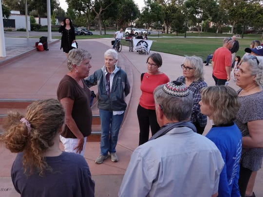 Rep. Julia Brownley, second from the left, speaks with attendees at a vigil against gun violence held at Camarillo's Constitution Park Sunday night, one of at least two local vigils after mass shootings in Texas and Ohio over the weekend killed 29.