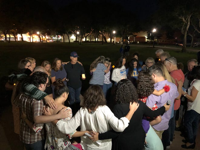 Attendees take part in a group hug at the end of a candlelight vigil in Camarillo Sunday night opposing gun violence after mass shootings in El Paso, Texas and Dayton, Ohio over the weekend killed 29 people.