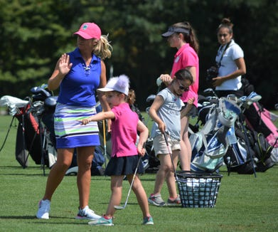 Westchester Country Club teaching professional Sarah Stone (left) sets up for a high-five in response to a good shot during the 11th annual Girls to the Tee clinic on August 5, 2019.