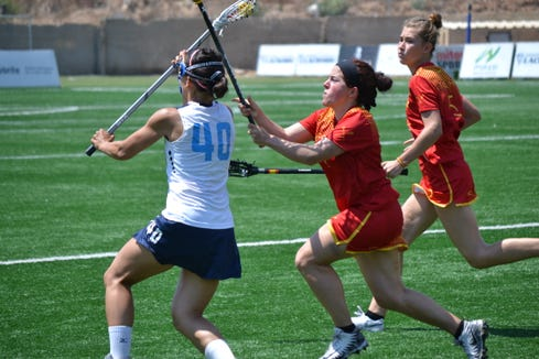 Sarah Quigley (in red), playing for Spain, tries to stop Italian player during the 2019 Women's Lacrosse European Championships.