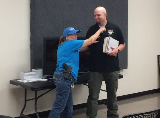 """Kathy Richardson, a Texas Licensed to Carry Handguns instructor, demonstrates how to use a cell phone as a deadly weapon with the help of Zach Ponder, a salesman for Texas Law Shield, which offers firearms legal defense plans in this June 7, 2018, file photo. Richardson helped out at a """"How to Survive an Active Shooter"""" seminar earlier in June at the High Caliber Gun Range."""