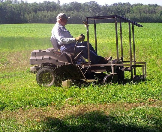 Bob caught cutting grass so we can continue to use the critter cam without grass growing in the camera's way.