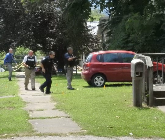 Zanesville police officers prepare to clear a residence where a young male was found Monday afternoon with a gunshot wound to the leg.