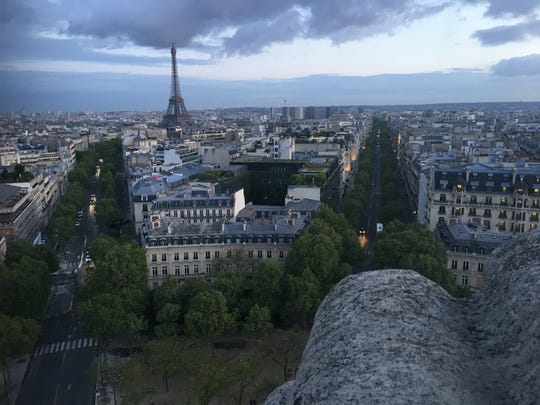 The Eiffel Tower and the rooftops of Paris at dusk, as seen from the top of the Arc de Triomphe.