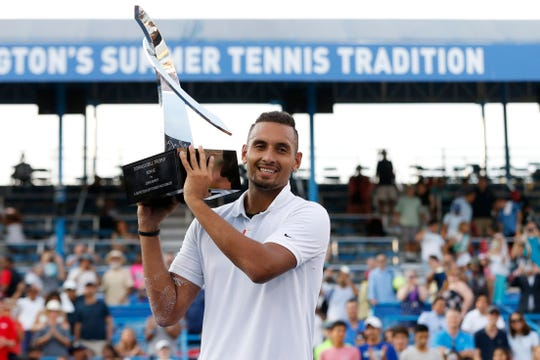 Nick Kyrgios celebrates with the Donald Dell Trophy after winning the Citi Open.