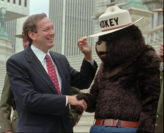 New York Gov. George Pataki, left, greets Smokey Bear after signing legislation in front of the Capitol in Albany, New York, Aug. 1, 1996.