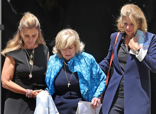 Maria Shriver, left, and Sydney Lawford McKelvy, right, help Courtney Kennedy Hill down the steps of the church after the funeral service for Hill's daughter, Saoirse, on Aug. 5, 2019.