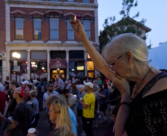 Cheryl MacGowan cries in front of Ned Pepper's Bar during a candlelight vigil for the victims of Sunday morning's shooting in Dayton Ohio, Aug. 4, 2019. . MacGowan had been in the area the