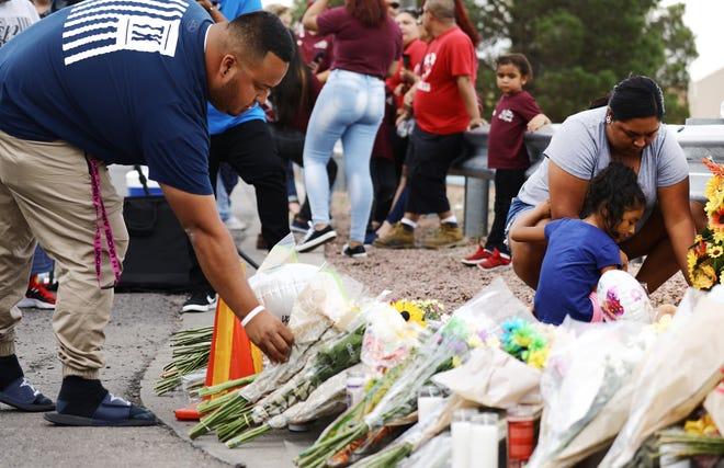 People leave flowers outside scene of shooting in El Paso, TX on August 4, 2019.