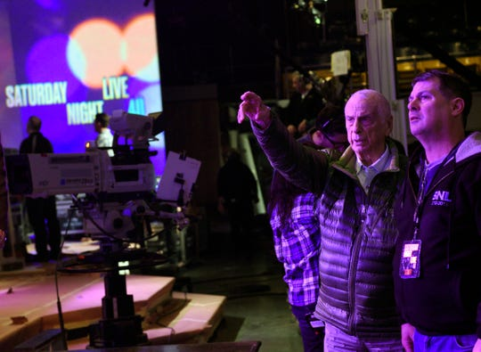 "This  Feb. 3, 2015 photo released by NBC shows lighting designer Phil Hymes, second right, with lighting director Geoff Amoral on the set of ""Saturday Night Live,"" in New York. NBC says Emmy-winning lighting director Hymes has died."